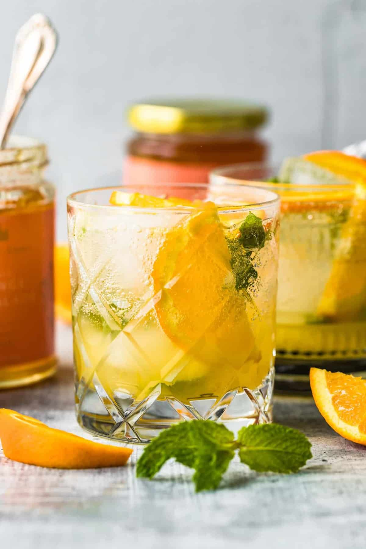 citrus smash cocktail on a table with sliced oranges and mint leaves