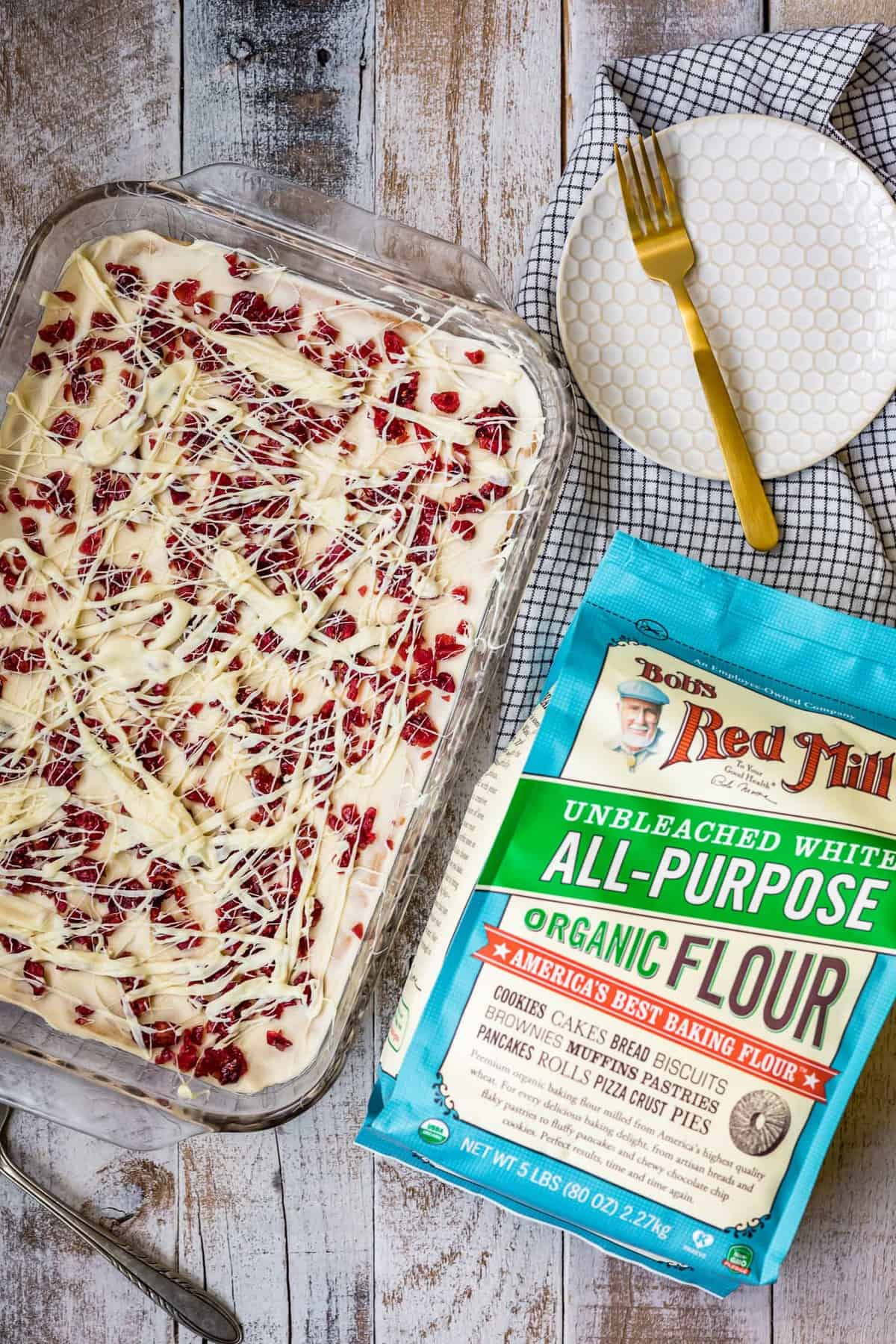 a baking dish of cranberry bars next to a bag of flour