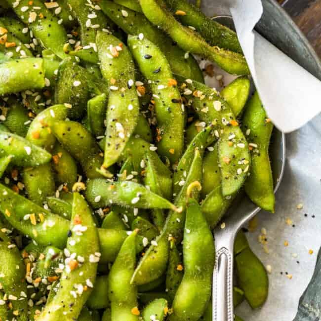 Bright green edamame in a bowl seasoned with a spoon