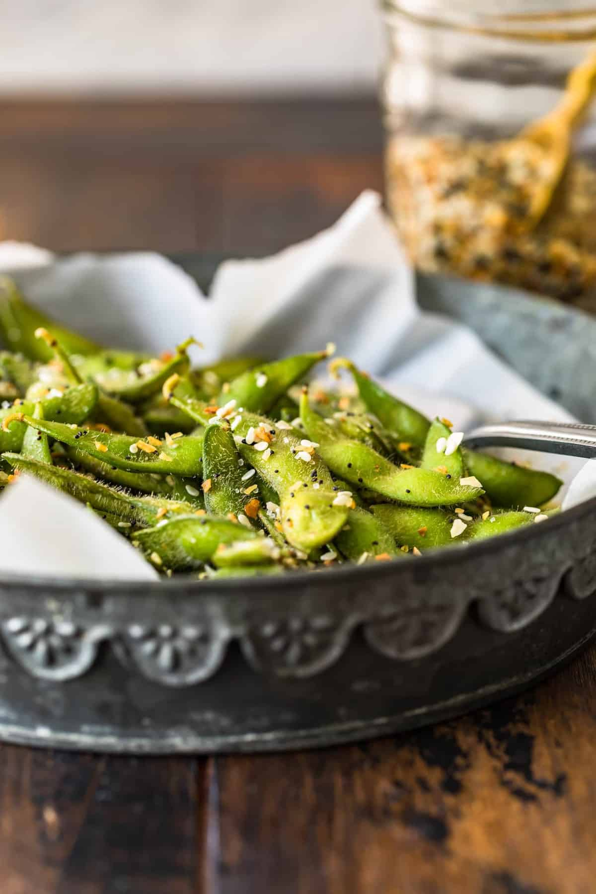 A side view of the edamame sitting in a silver dish with a spoon