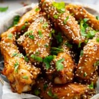 honey glazed chicken wings topped with sesame seeds and cilantro in a bowl
