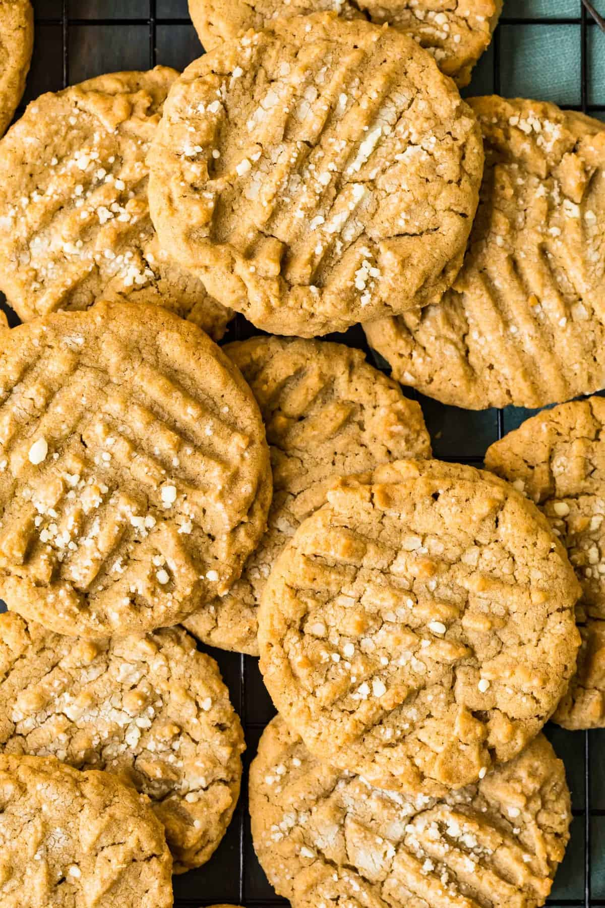 A pile of peanut butter cookies on a cooling rack