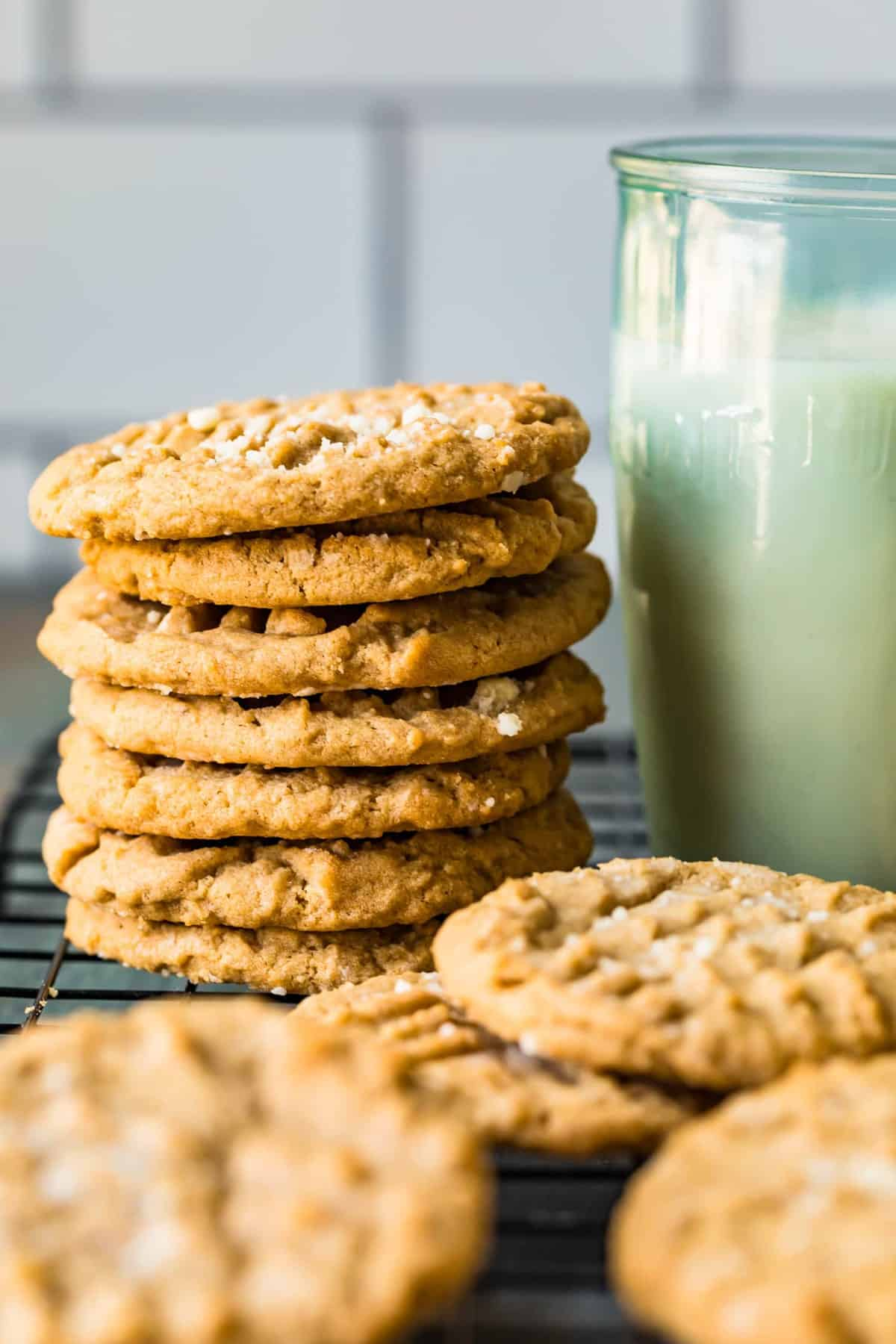 A stack of peanut butter cookies next to a glass of milk