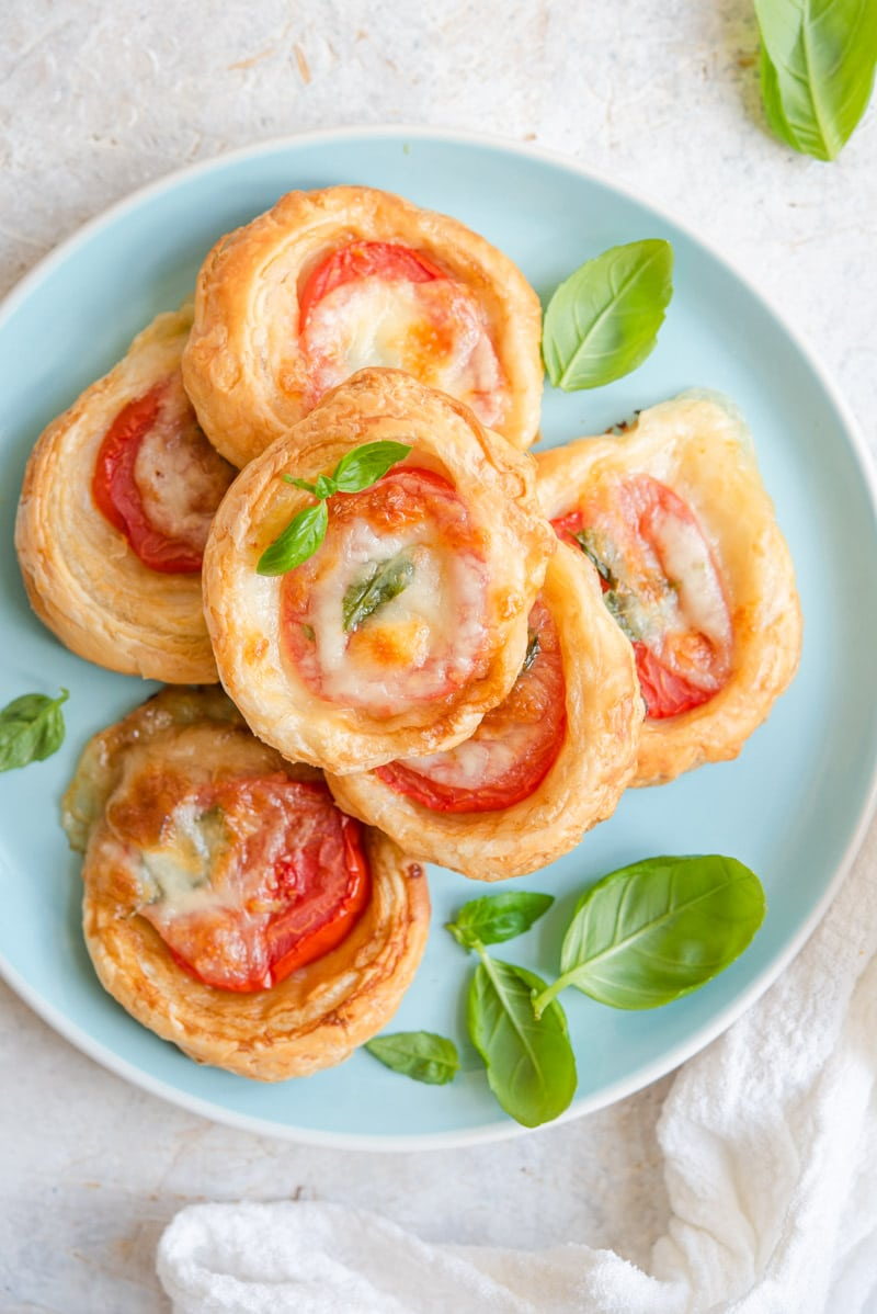 An overhead shot of caprese tarts on a blue plate