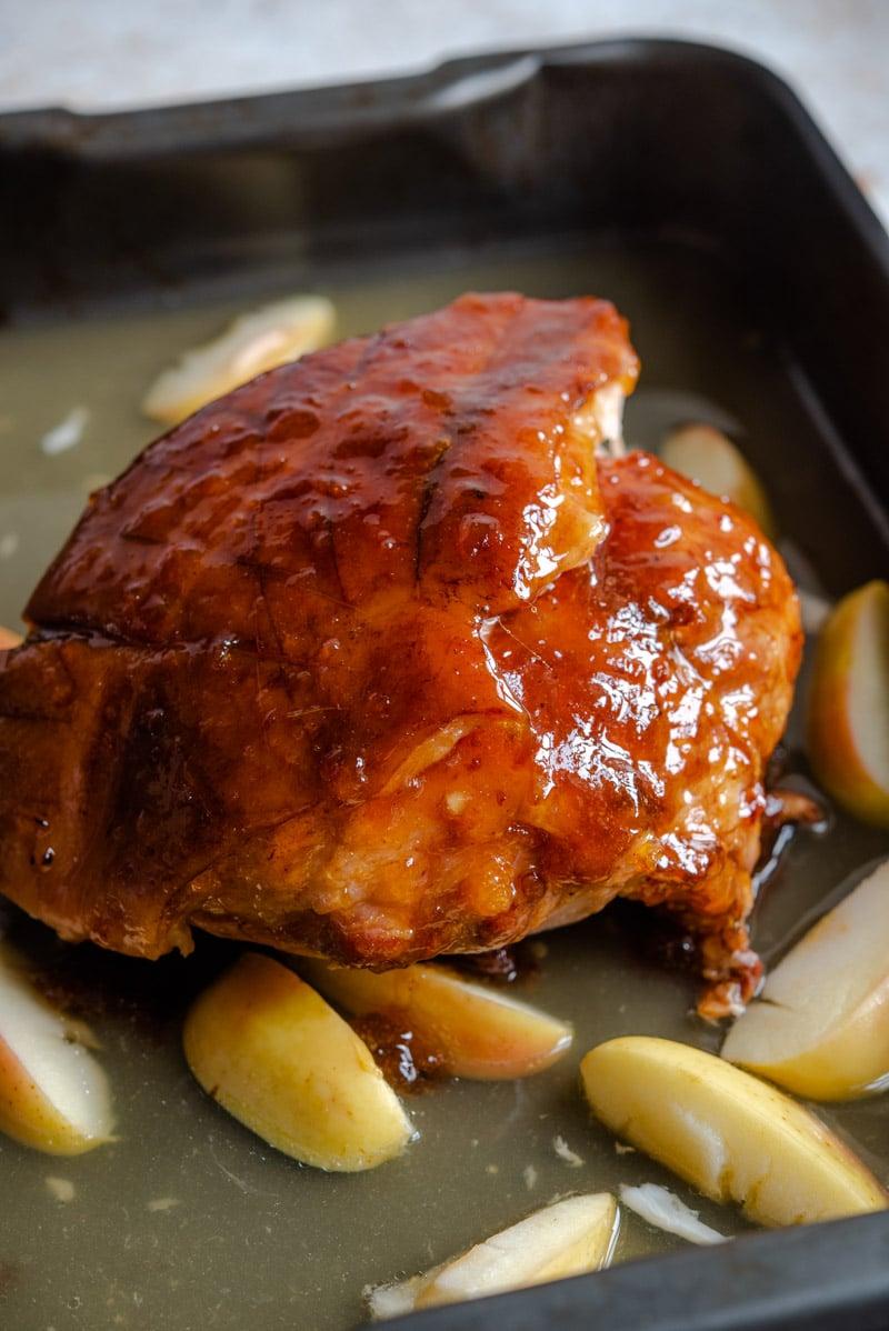 A glazed ham half way through cooking