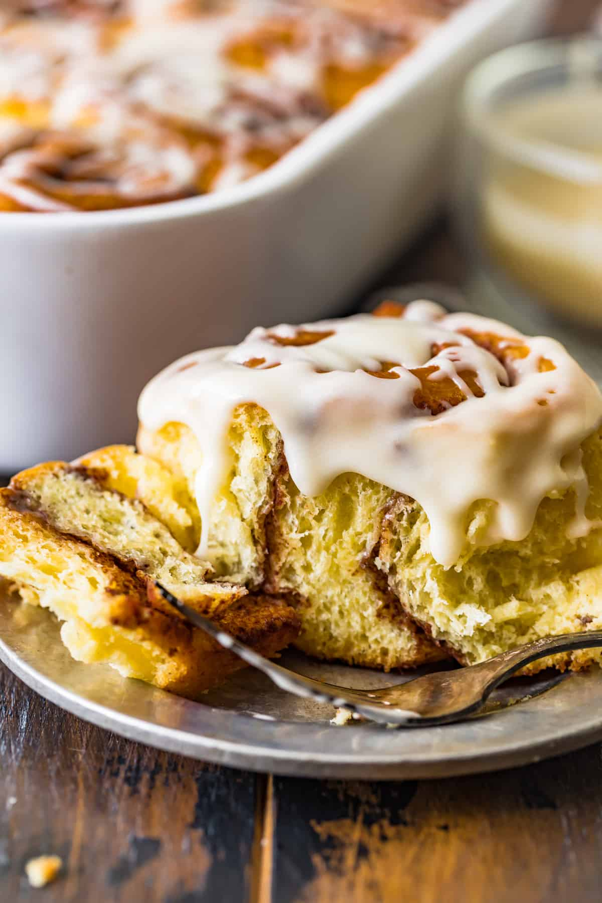 A Homemade Cinnamon Roll with icing on a plate