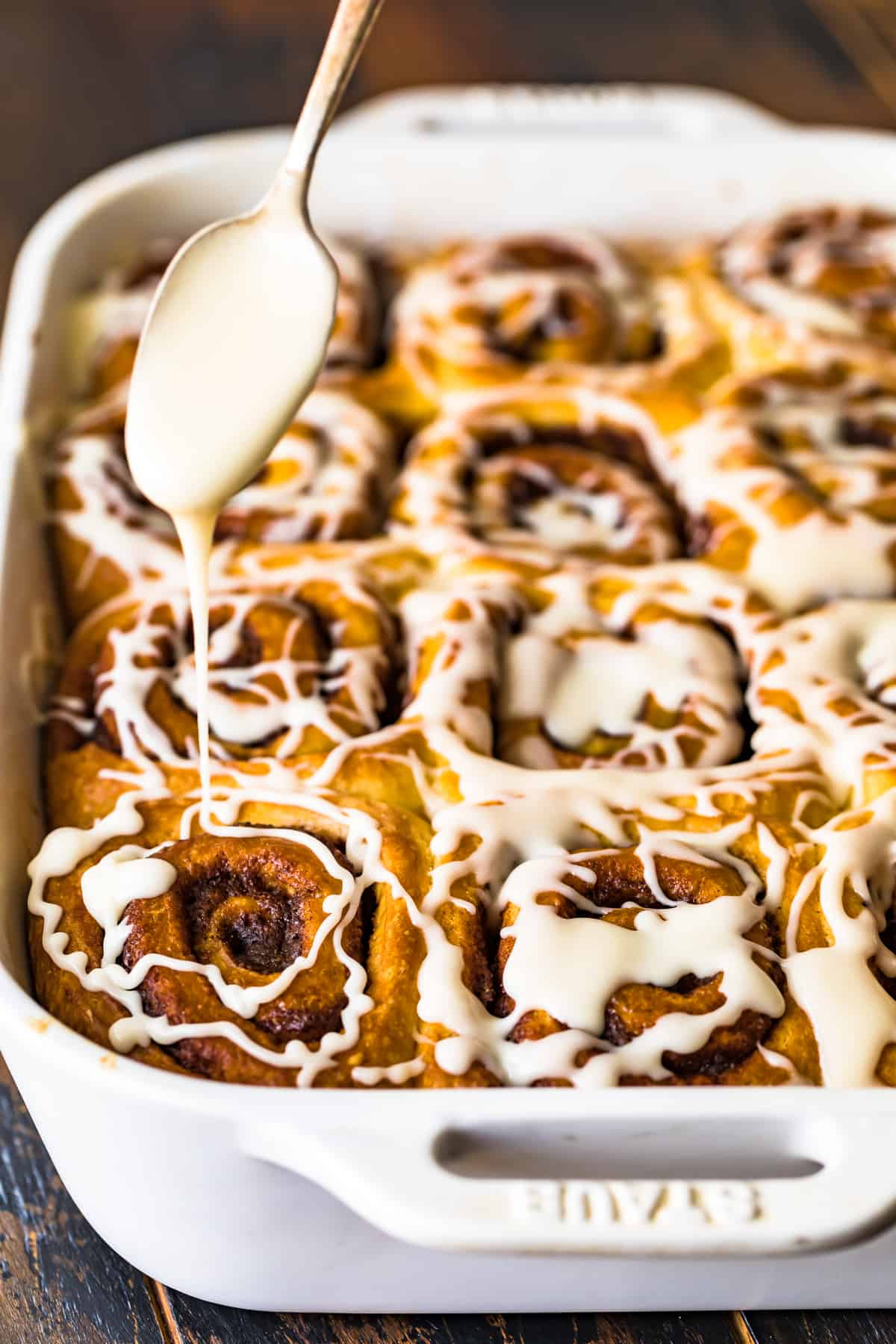 Icing on a spoon being drizzled over the rolls