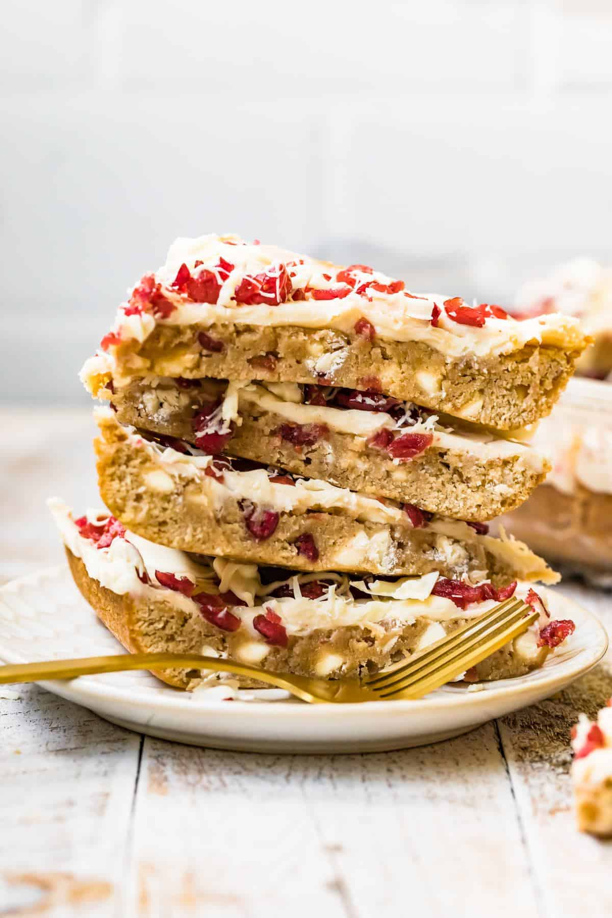 stacked cranberry bliss bars on a plate
