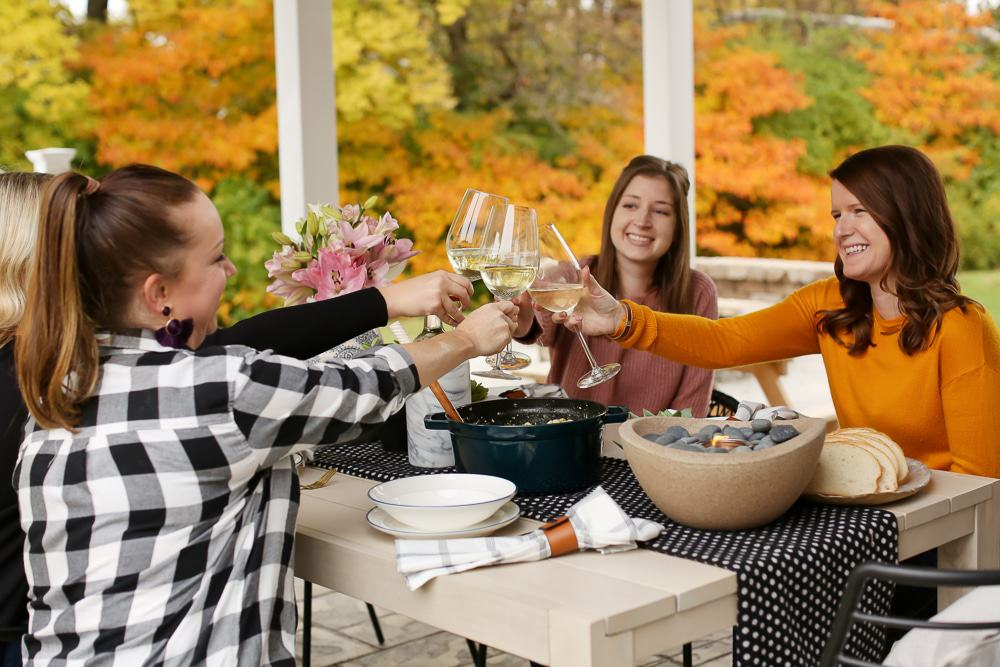 four women sitting at a table outside using wine glasses to cheers with fall foliage behind them