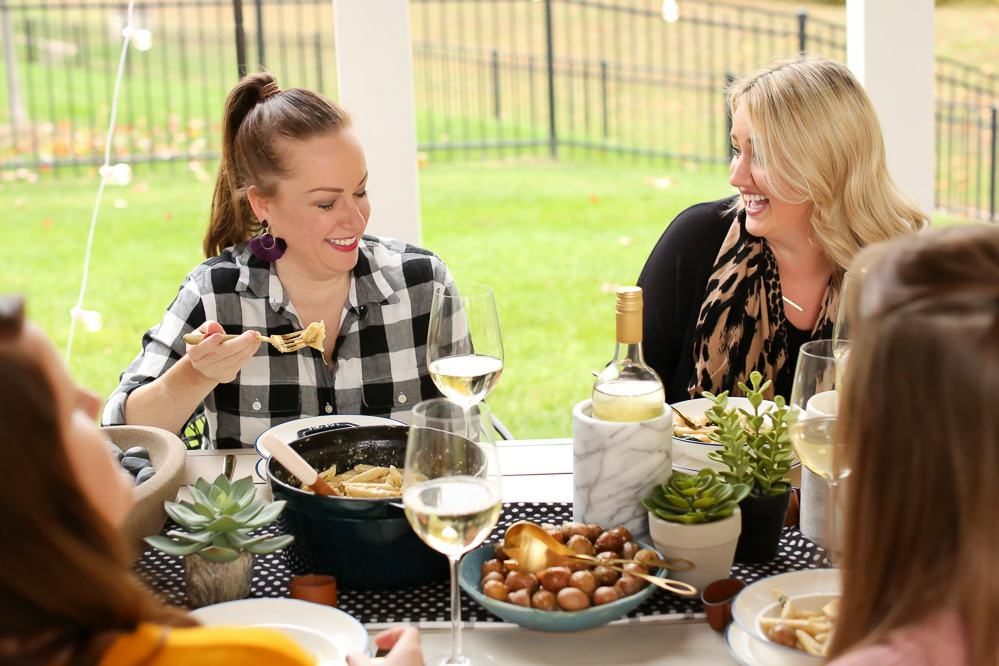 a group of women eating at a table outside laughing