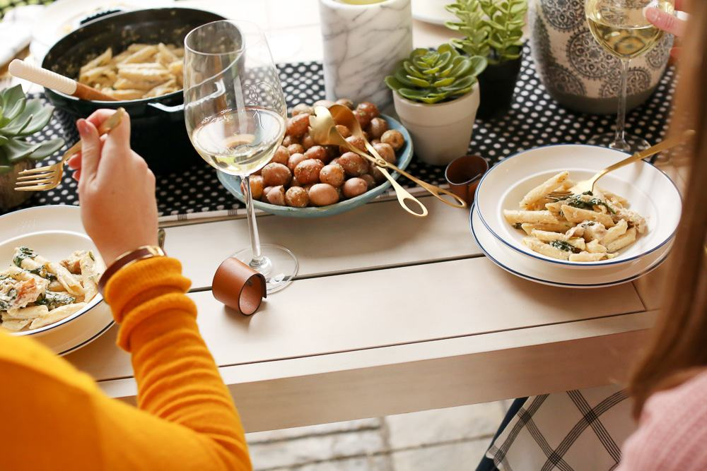 over the top shot of a table with bowls of pasta, potatoes, wine glasses, and people eating