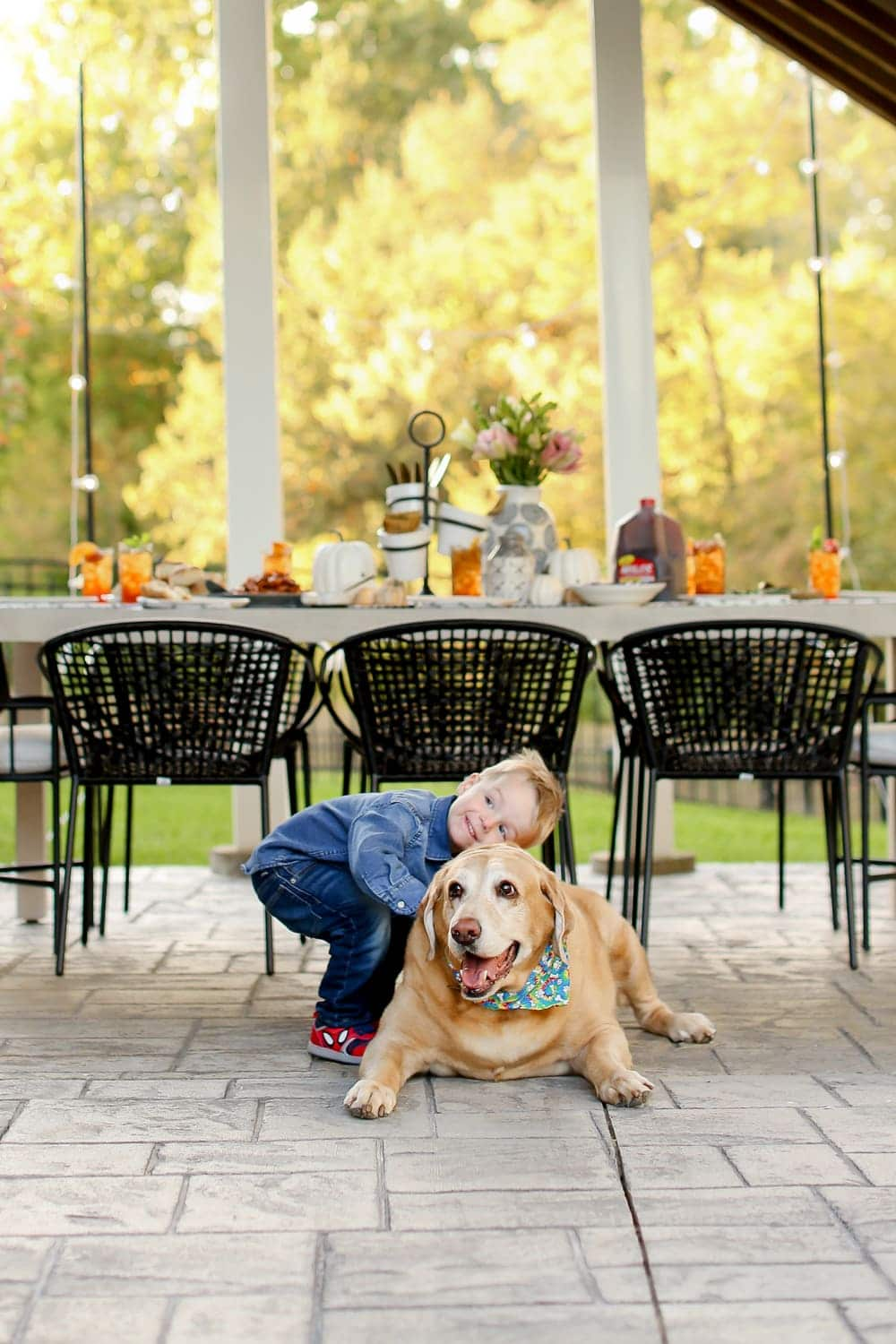 A toddler boy hugging a yellow labrador retriever with a table behind them.