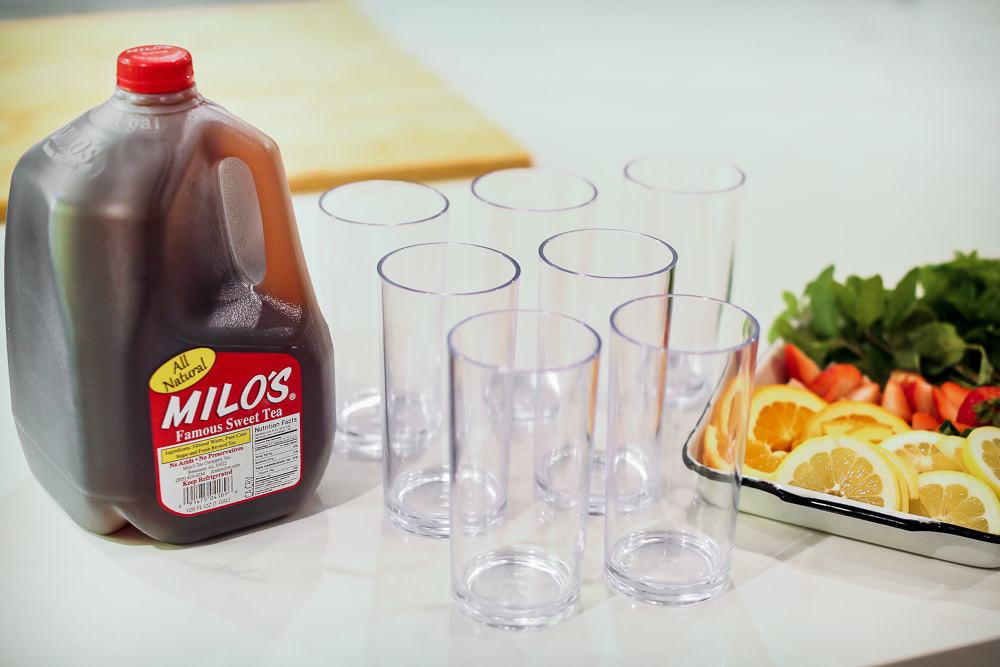 A gallon of Milo's Sweet Tea and glasses sitting on a table