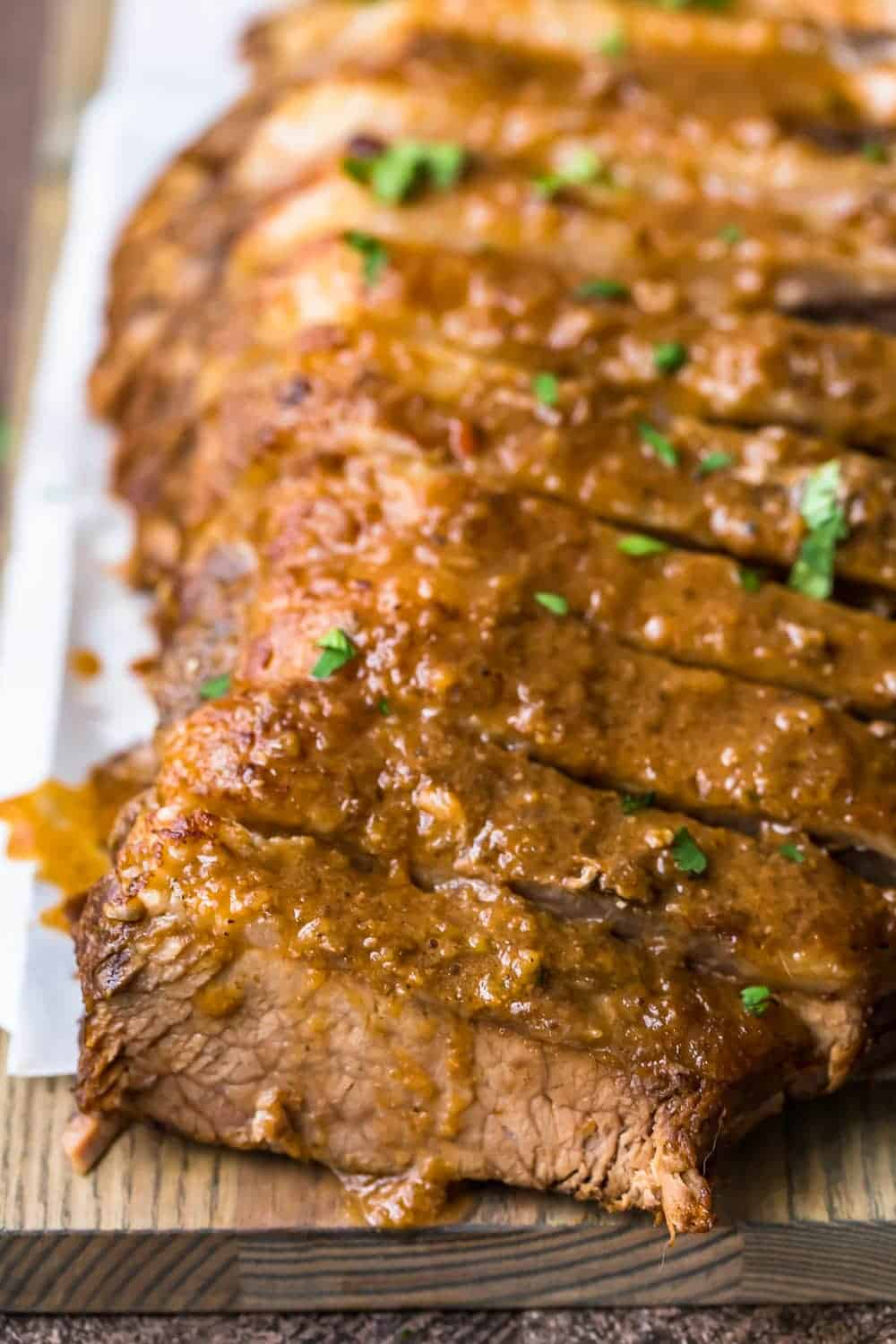 Sweet and sour brisket on a wooden chopping board