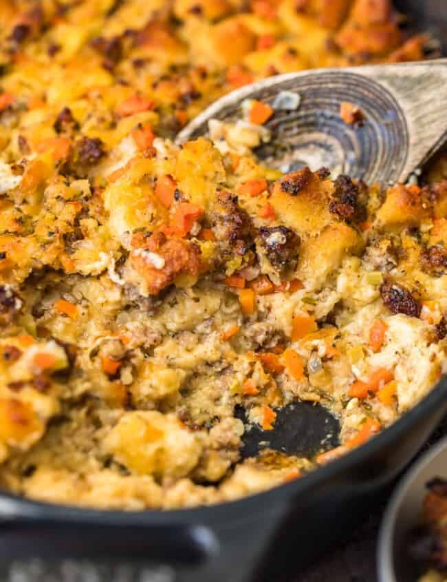 spoon scooping up sausage stuffing in skillet