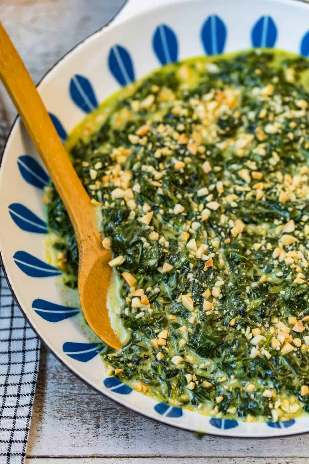 A wooden spoon in cooked creamed spinach