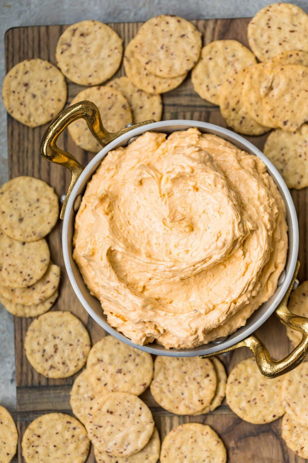 Top shot of a bowl of Beer Cheese Dip with crackers on a board