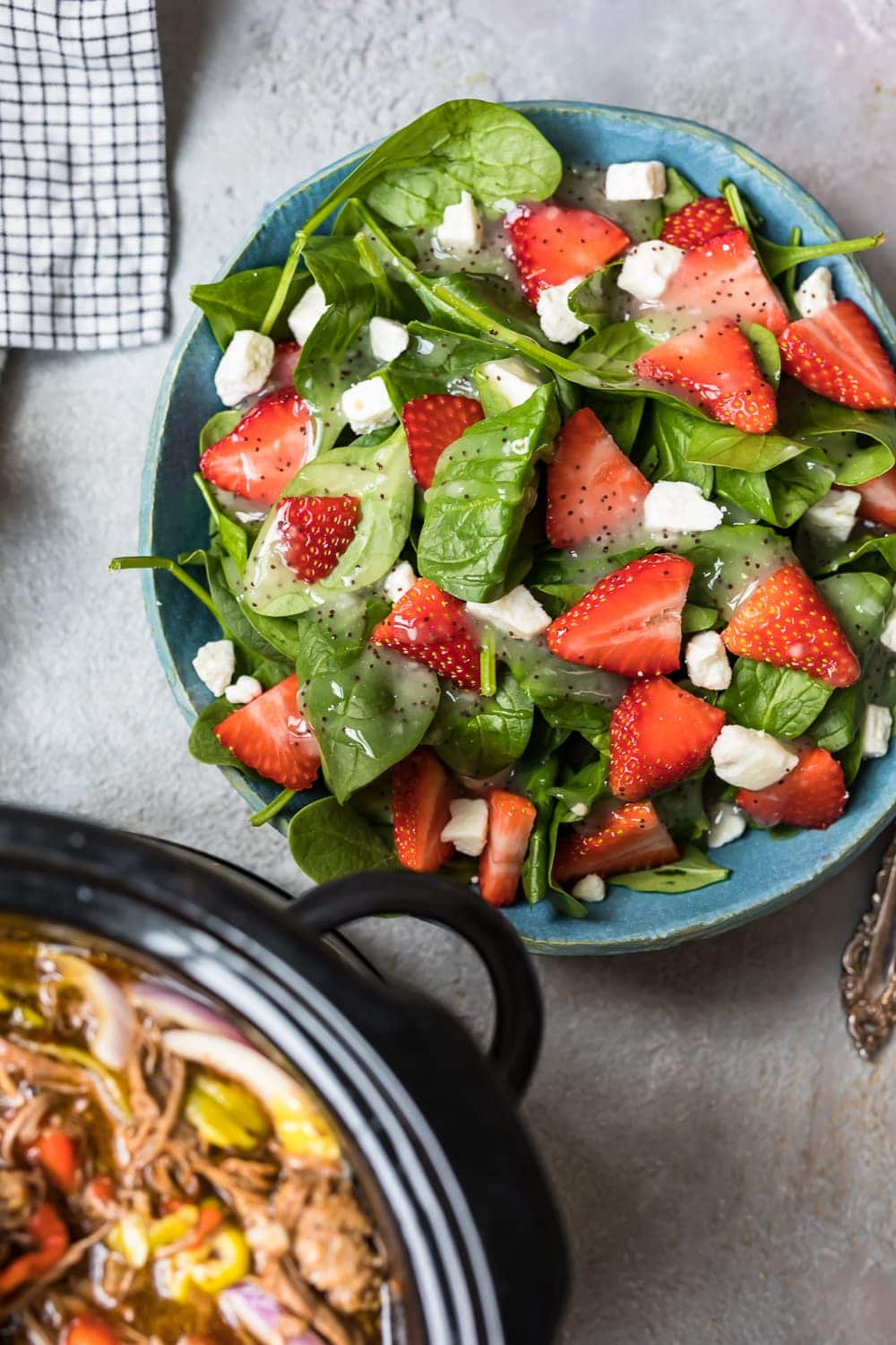 a plate of salad with strawberries and feta cheese
