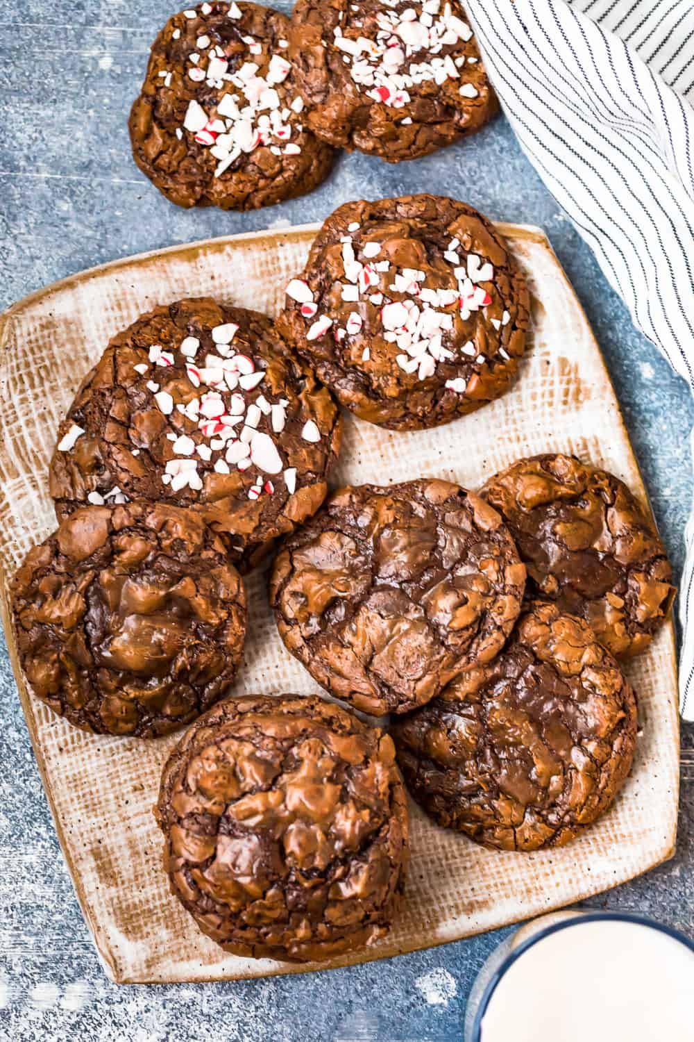 a mix of fudgy brownie cookies on a plate, some cookies with crushed peppermint candy on top