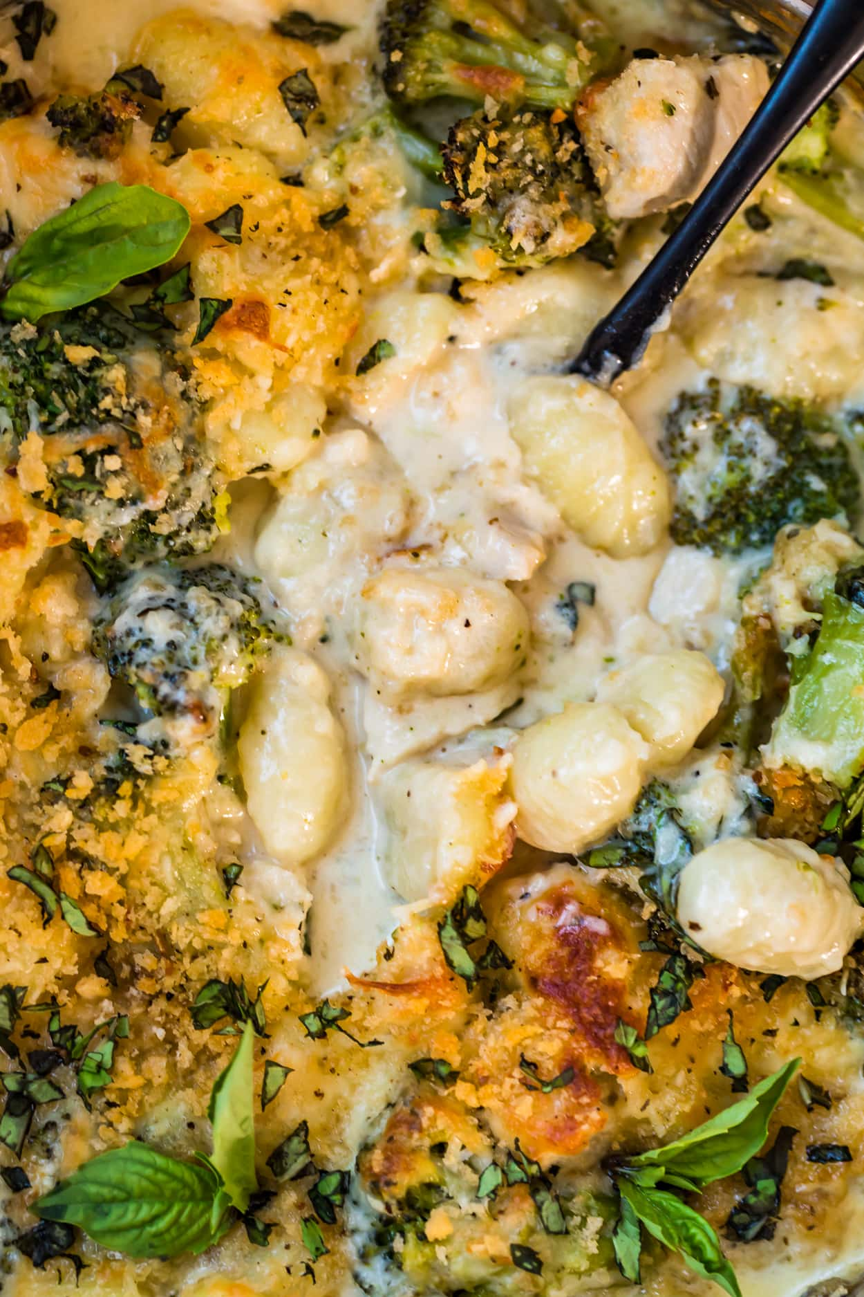 Close up view of Chicken Alfredo Gnocchi Bake with a black spoon