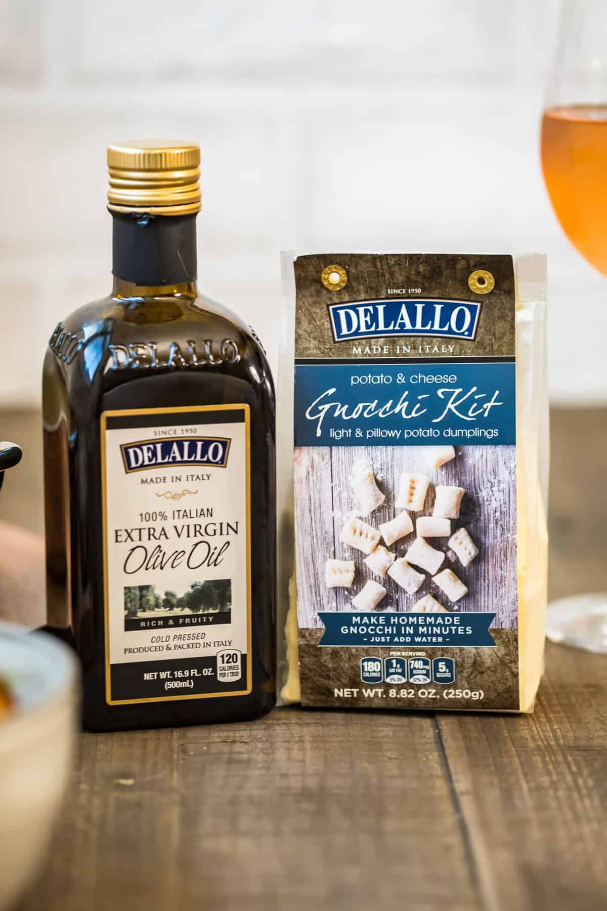Delallo extra virgin olive oil bottle and Delallo Gnocchi Kit on wooden table