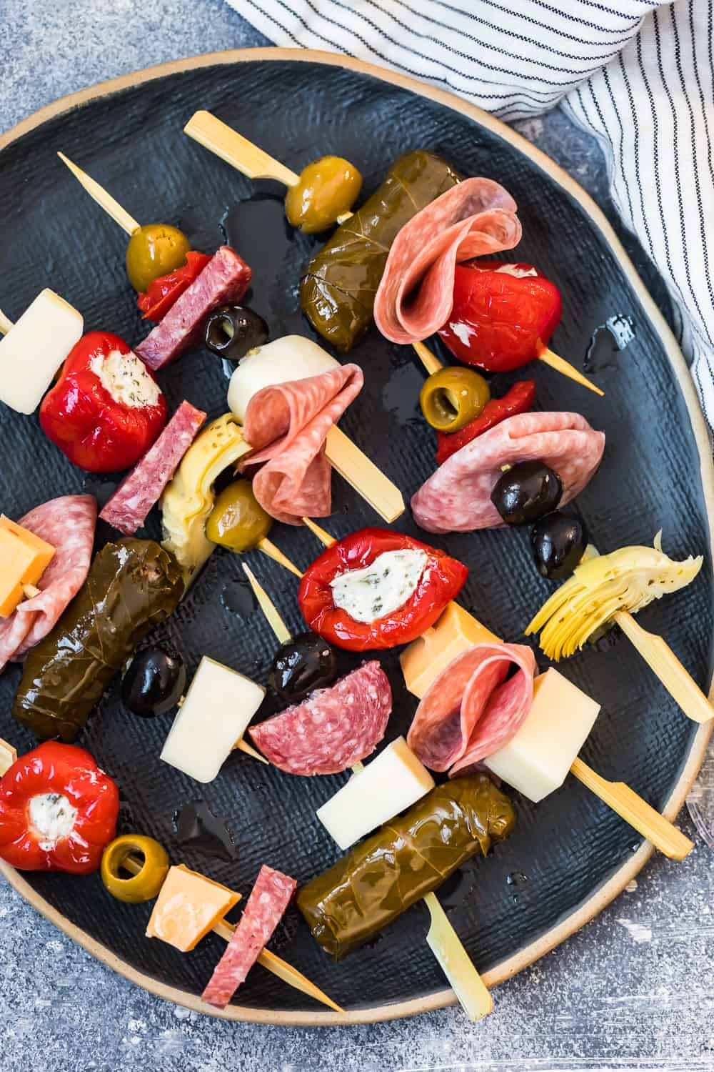 several antipasti skewers on a black plate