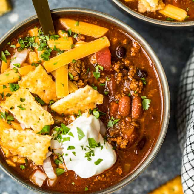 crockpot chili in a bowl with spoon with crackers