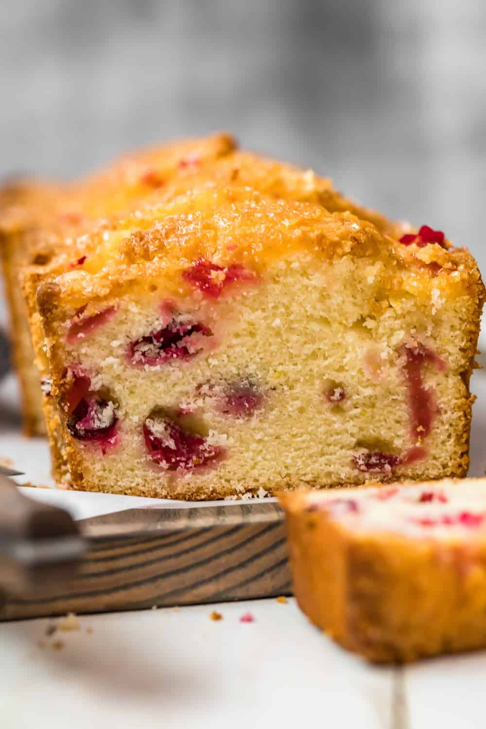 Glazed Lemon Cranberry Bread on a wooden chopping board
