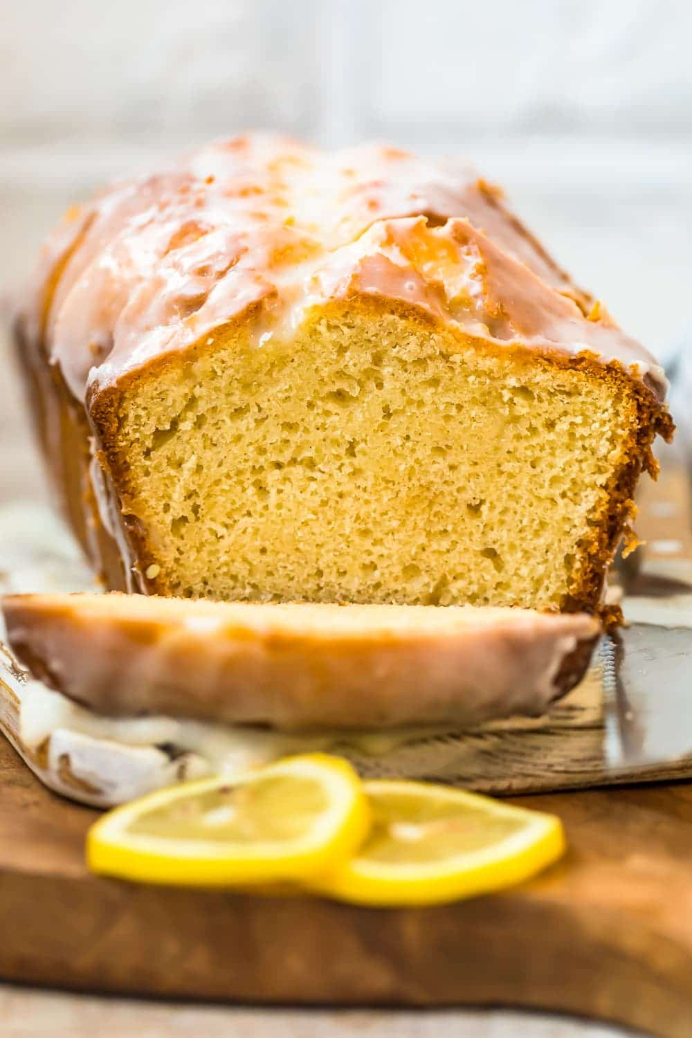 iced lemon loaf cake on a wooden cutting board