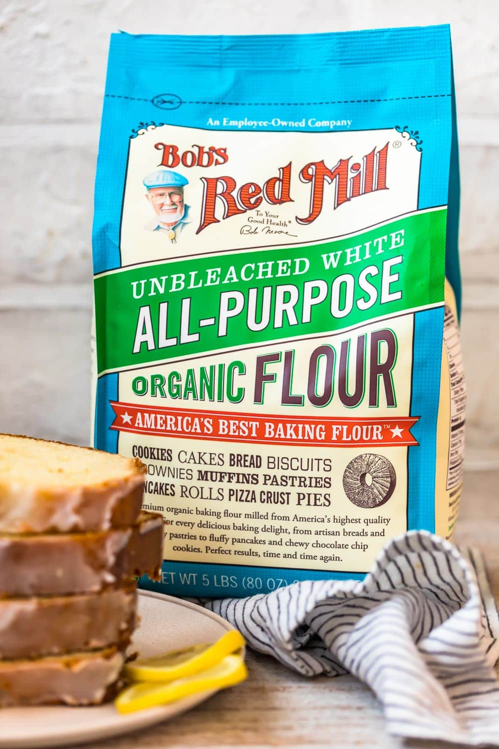 bob's red mill unbleached white all-purpose organic flour bag and a stack of bread slices on a plate