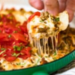 queso fundido in green dish with chip scooping dip