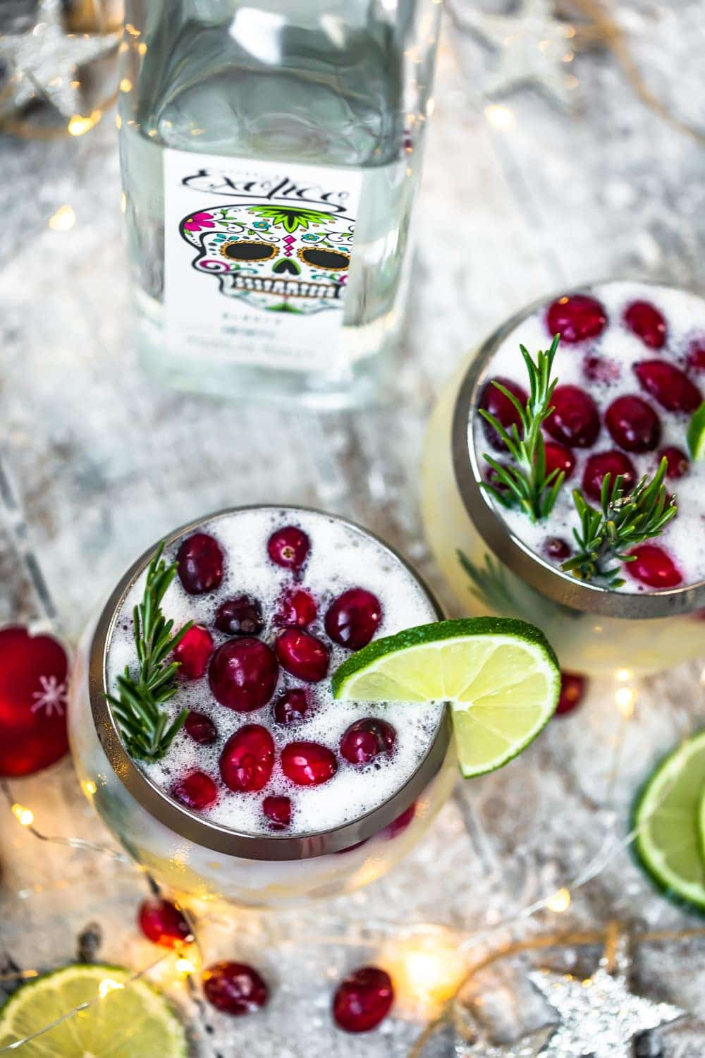 christmas cocktail topped with rosemary and cranberries