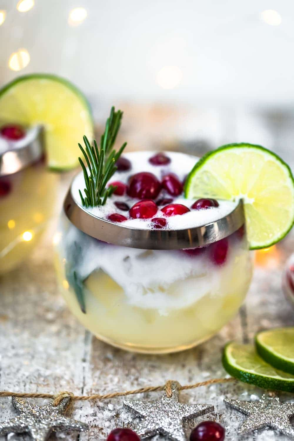 christmas cocktail topped with cranberries, rosemary, and lime