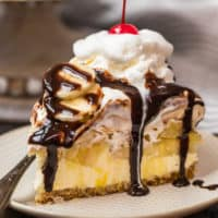 a slice of banana split cake on a plate drizzled in chocolate syrup