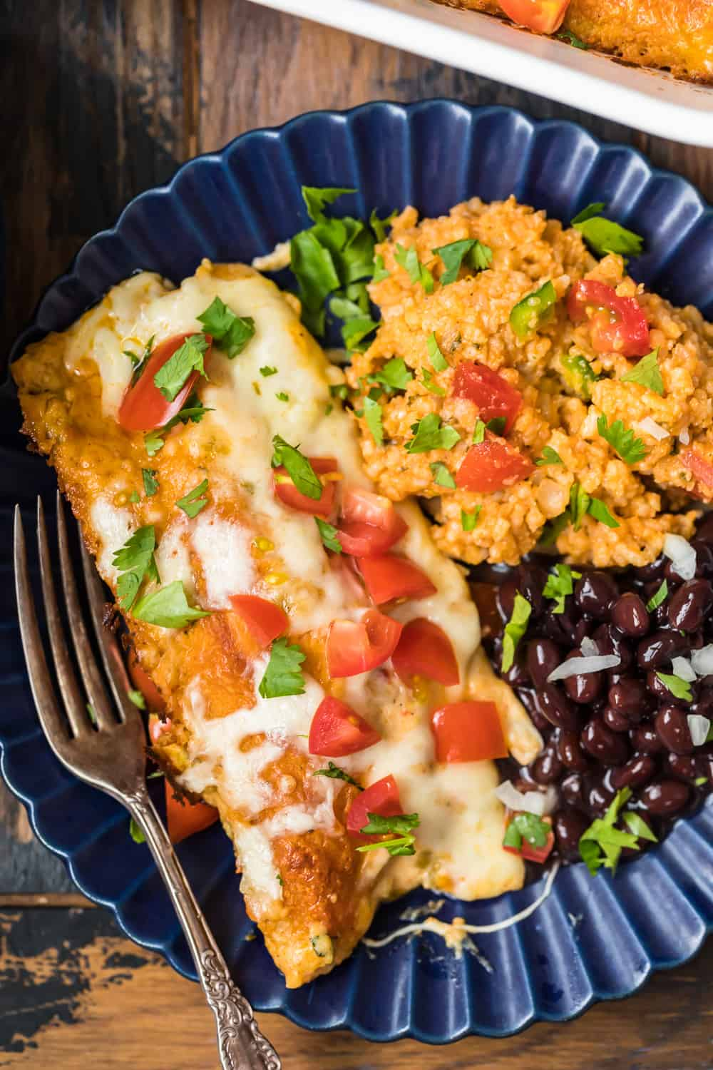creamy chicken enchilada on plate with beans