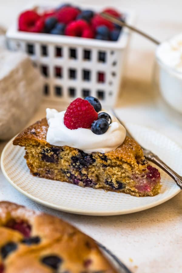 A slice of Blueberry Raspberry Coffee Cake topped with cream