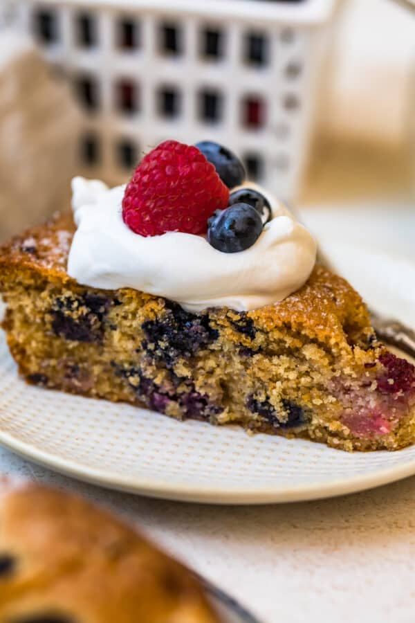Blueberry Raspberry Coffee Cake served on a white plate with cream and fresh fruits