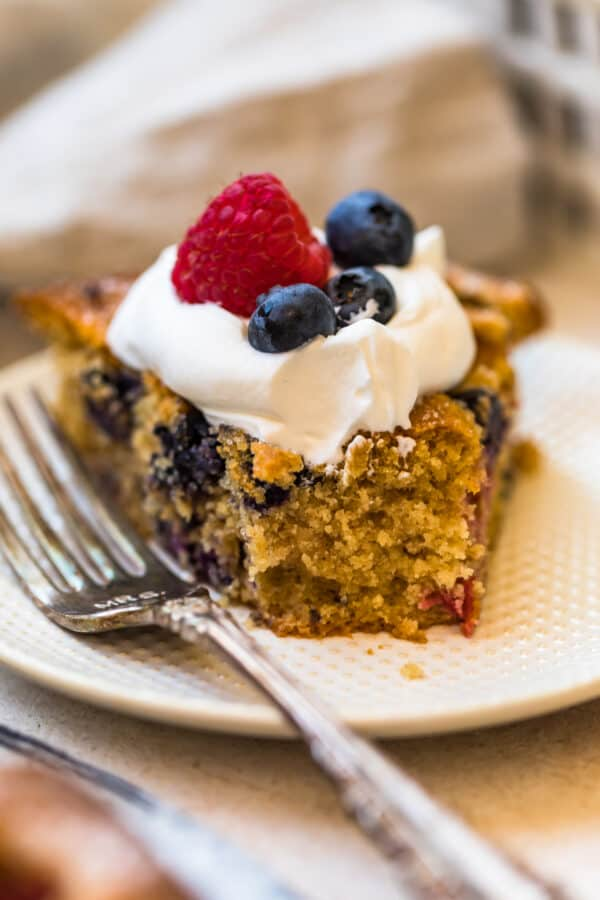 A slice of Blueberry Raspberry Coffee Cake with a forkful cut off of the end