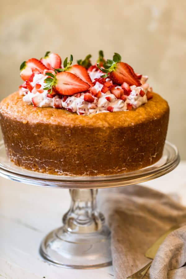 A Kentucky butter cake topped with strawberries and cream on a cake stand