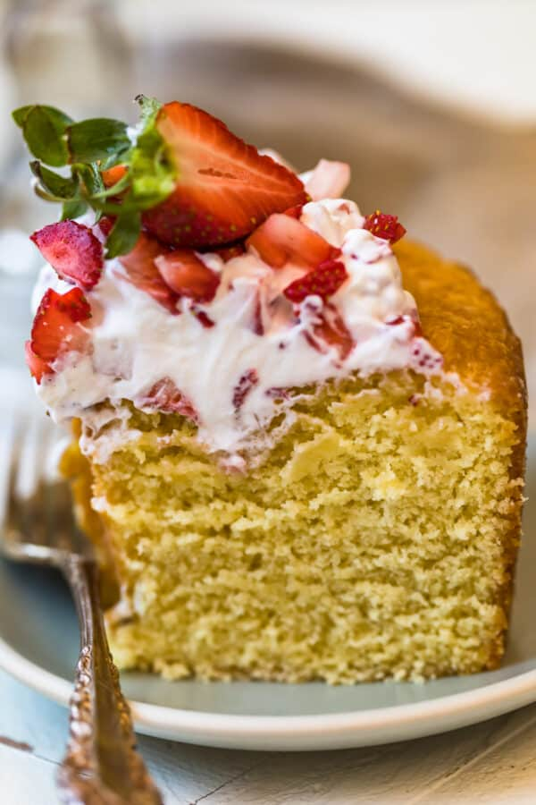 Close up of a slice of the cake with strawberries and cream topping