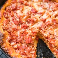 chicago style deep dish pizza in skillet with piece missing