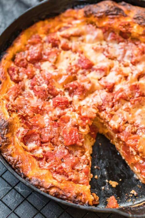 A chicago deep dish pizza with a slice taken out of it