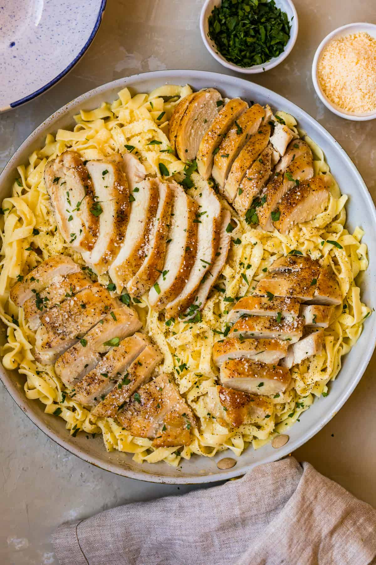 Sliced chicken breast on top of the pasta