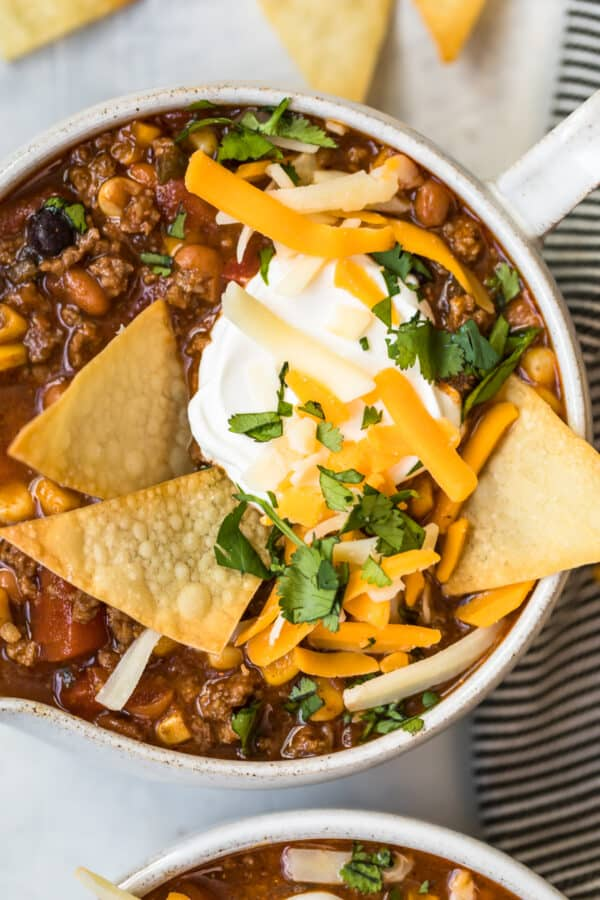 taco soup topped with sour cream and tortillas