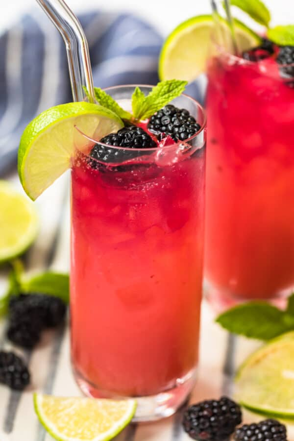 blackberry paloma in glass surrounded by limes and blackberries