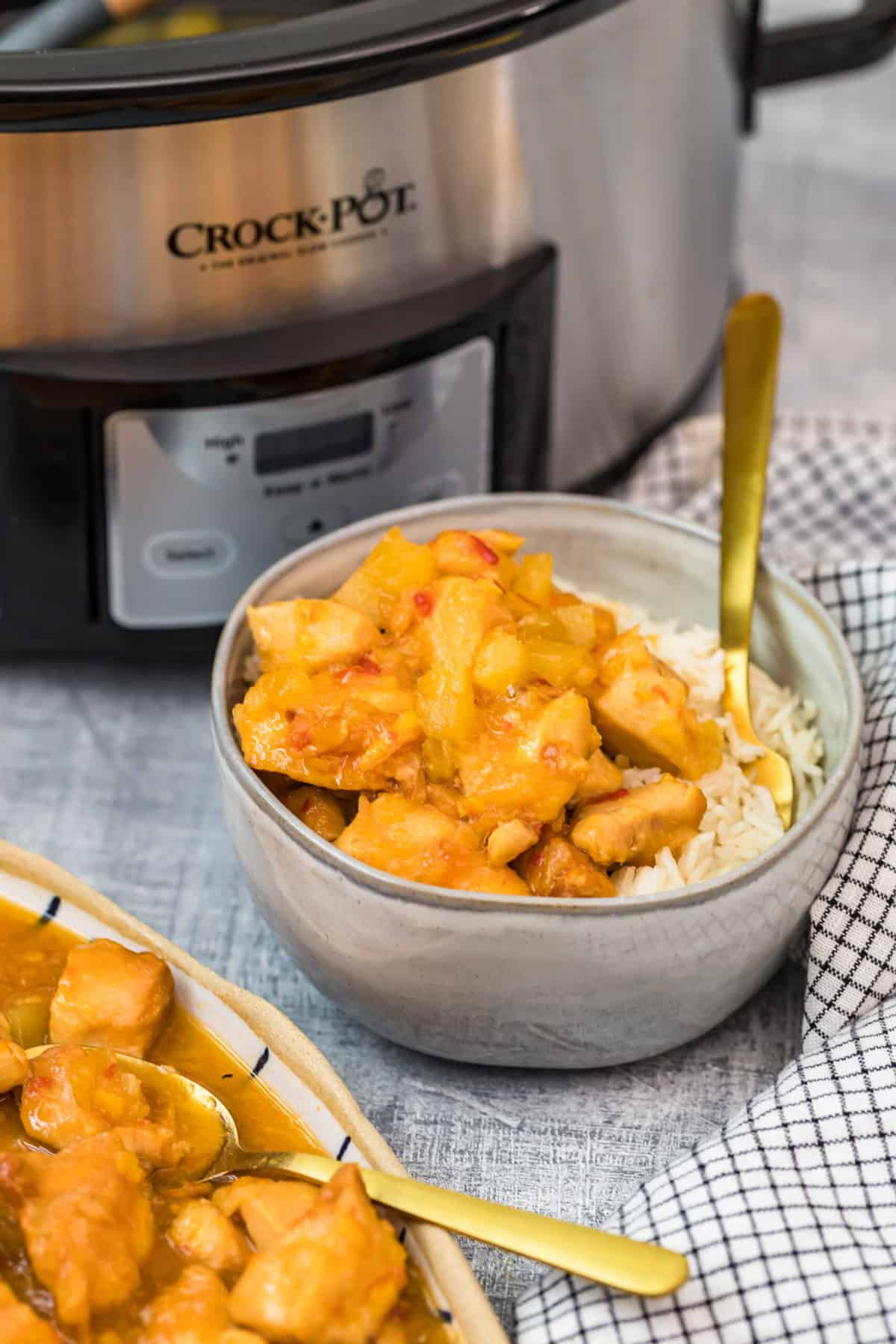 crock pot sweet and sour chicken in a bowl with rice on a table