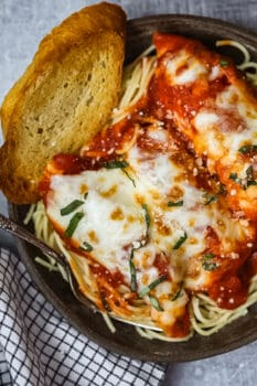 a bowl of chicken parmesan with a slice of bread