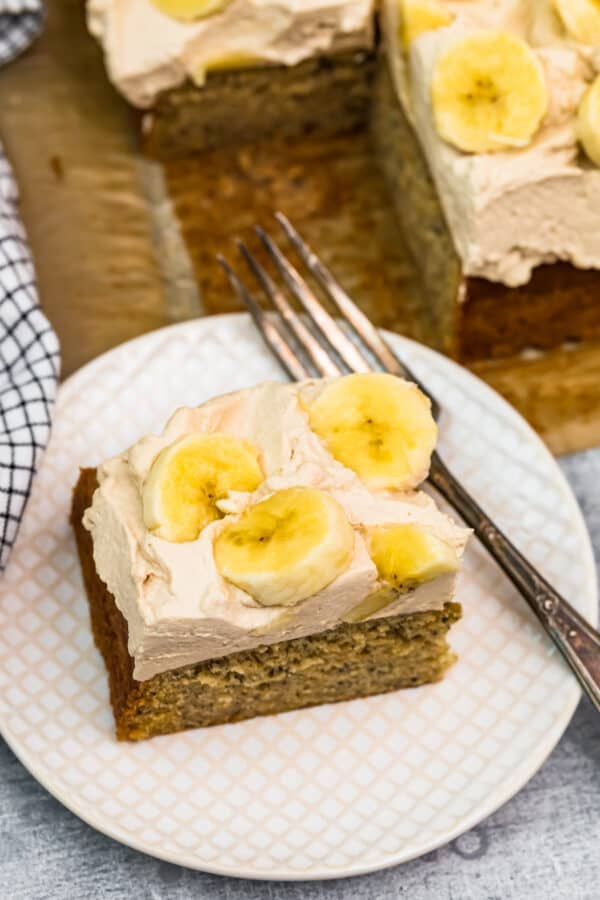 slice of banana cake with whipped cream and bananas