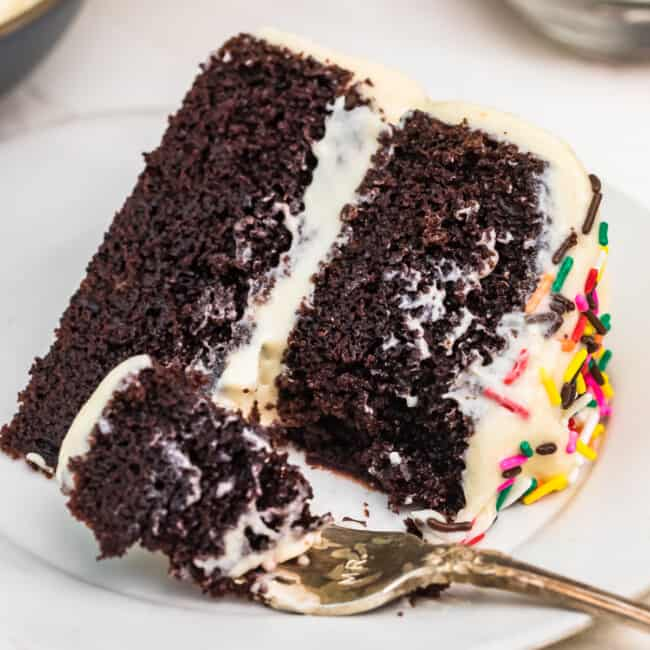 A piece of chocolate cake on a plate, with Icing and fork