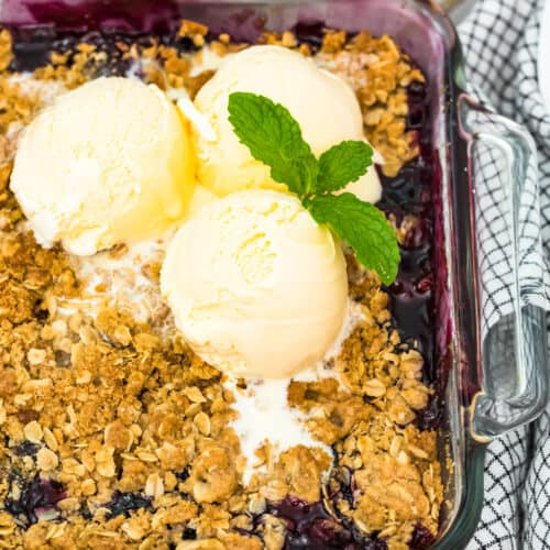 berry crisp in baking dish topped with 3 scoops ice cream